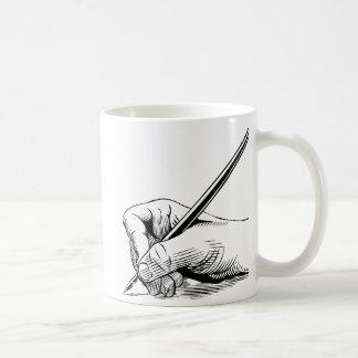 Pluma de tenencia de la mano taza de café