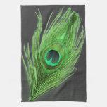 Pluma verde del pavo real en la toalla de cocina n