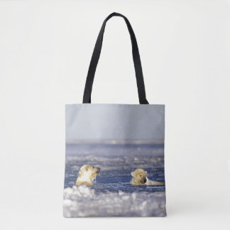 Polar bear cubs playing in pack ice of the tote bag