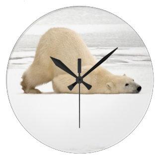 Polar bear scratching itself on frozen tundra large clock