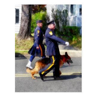 Policía y perro policía en desfile postales