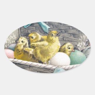 Polluelos en cesta con los huevos y las flores pegatina ovalada