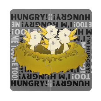 Polluelos hambrientos en una jerarquía posavasos de puzzle