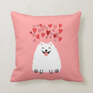 Pomeranian blanco feliz con los corazones rosados almohada