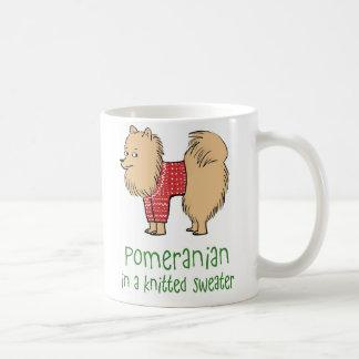 Pomeranian en un suéter hecho punto taza de café