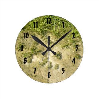 Pond grass and sand background round clock