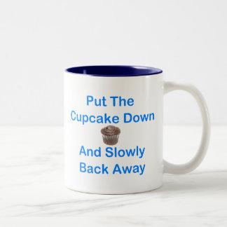 Ponga la magdalena abajo y lentamente detrás lejos taza