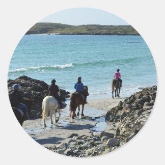 Pony trekking along the beach round stickers