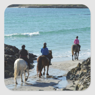 Pony trekking along the beach square stickers