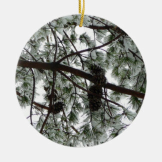 Por debajo la foto nevada del invierno del árbol adorno navideño redondo de cerámica