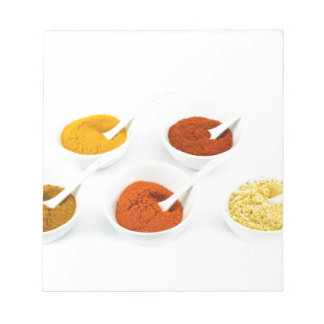 Porcelain bowls and spoons with various spices notepad