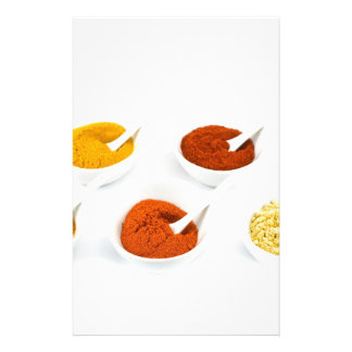 Porcelain bowls and spoons with various spices stationery
