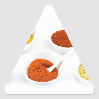 Porcelain bowls and spoons with various spices triangle sticker