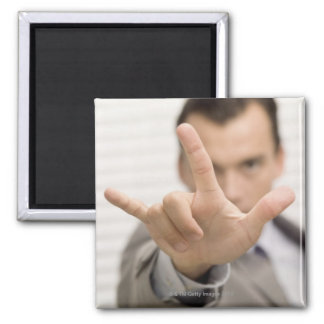 Portrait of a businessman making a hand sign magnet
