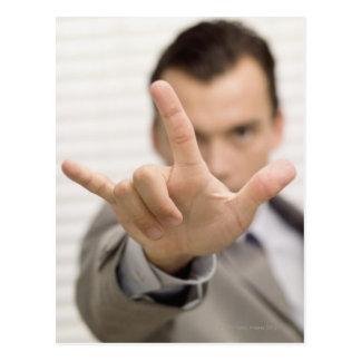 Portrait of a businessman making a hand sign postcard