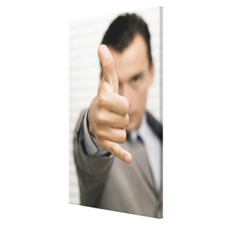 Portrait of a businessman making a thumbs up canvas print