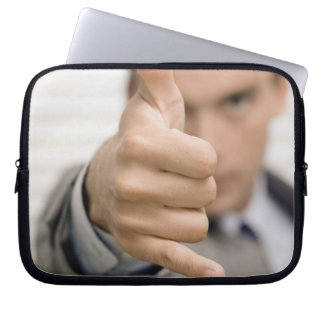 Portrait of a businessman making a thumbs up computer sleeve