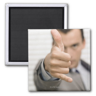 Portrait of a businessman making a thumbs up magnet