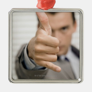 Portrait of a businessman making a thumbs up metal ornament