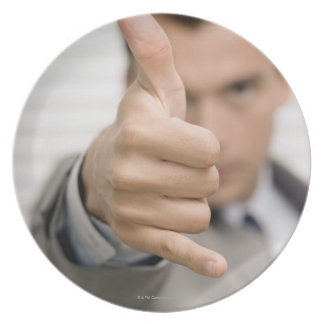Portrait of a businessman making a thumbs up plate