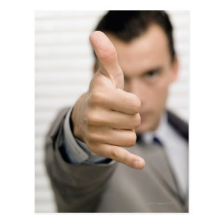 Portrait of a businessman making a thumbs up postcard