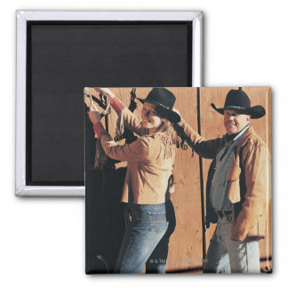 Portrait of a Cowboy and Cowgirl Arranging Reins Magnet