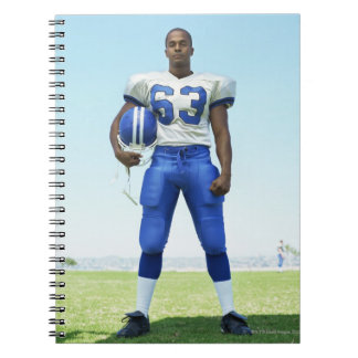 portrait of a football player holding a football spiral notebook