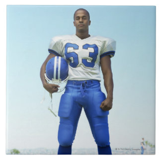 portrait of a football player holding a football tile