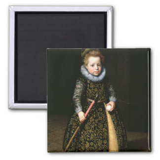 Portrait of a four-year old boy with club and 2 inch square magnet