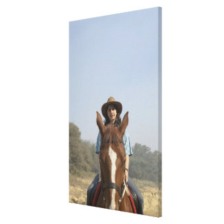Portrait of a teenage girl riding a horse canvas print