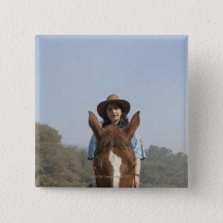 Portrait of a teenage girl riding a horse pinback button