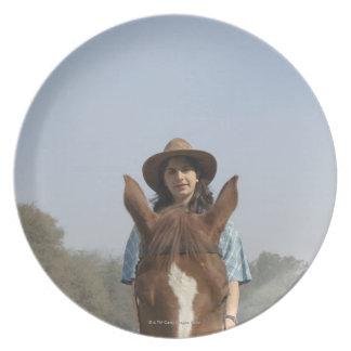 Portrait of a teenage girl riding a horse plate