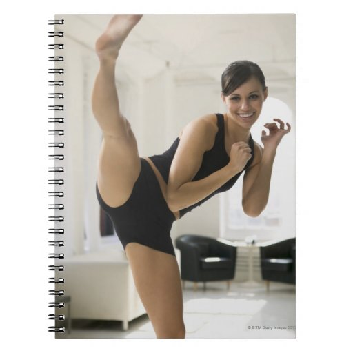 Portrait of a woman kicking spiral notebook