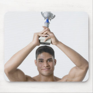 Portrait of a young man holding a trophy mouse pad