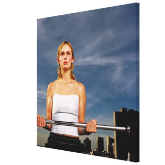 Portrait of a young woman carrying a barbell canvas print