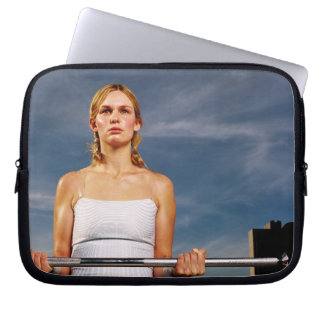 Portrait of a young woman carrying a barbell computer sleeves