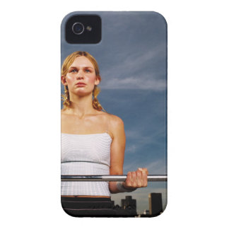 Portrait of a young woman carrying a barbell iPhone 4 cover