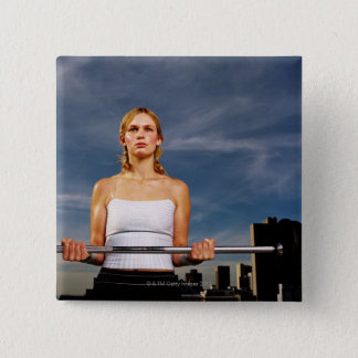 Portrait of a young woman carrying a barbell pinback button