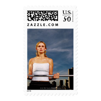 Portrait of a young woman carrying a barbell postage