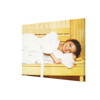 Portrait of a young woman lying in a sauna canvas print
