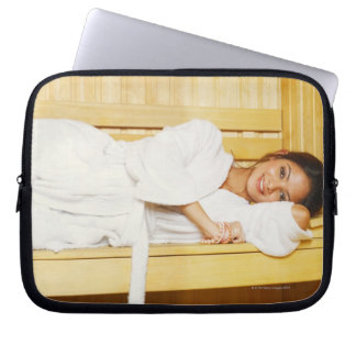Portrait of a young woman lying in a sauna laptop sleeve