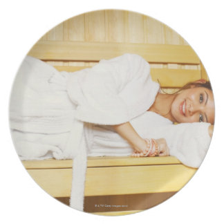 Portrait of a young woman lying in a sauna melamine plate