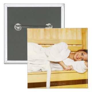 Portrait of a young woman lying in a sauna pinback button
