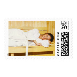 Portrait of a young woman lying in a sauna postage