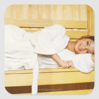 Portrait of a young woman lying in a sauna square sticker