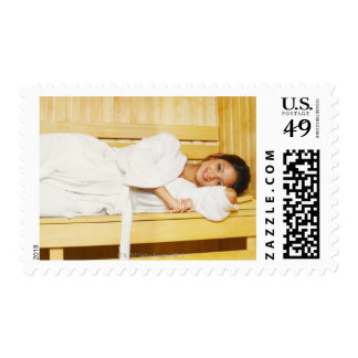 Portrait of a young woman lying in a sauna stamp