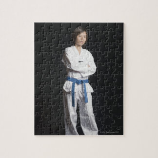 Portrait of a young woman standing with her arms puzzle