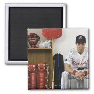 Portrait of baseball player sitting in locker magnet