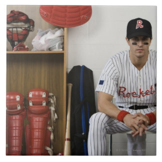 Portrait of baseball player sitting in locker tile