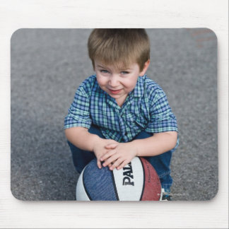 Portrait of boy with basketball outdoors mouse pad